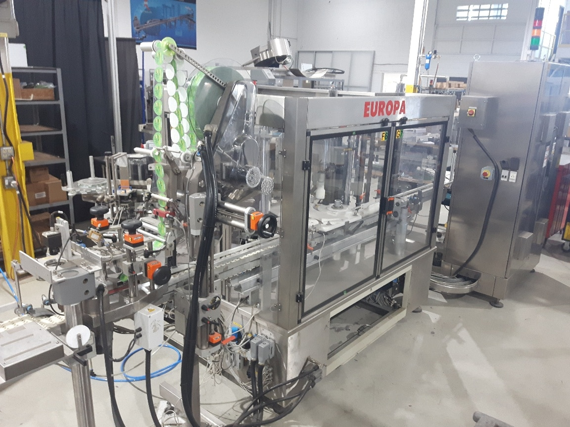 Used Harland rotary 2 head front & back labeler model Europa with top label applicator at exit